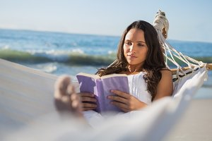 Content woman lying on hammock reading book