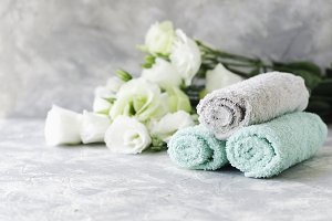 stack of towels with flowers for spa space under the text, selective focus