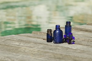 dark blue vintage bottle of oil on wooden platform in the pool background, selective focus