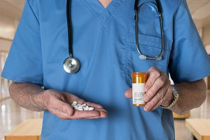 Senior doctor in scrubs with RX tablets
