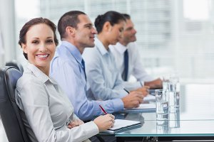 Businesswoman smiling at camera while her colleagues listening to presentation