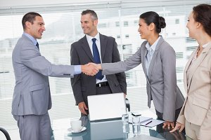 Cheerful business people meeting and shaking hands