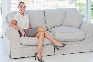 Attractive blonde businesswoman posing sitting on sofa