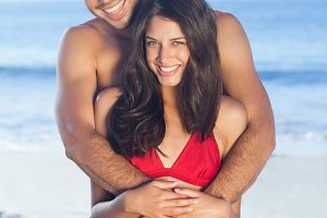 Happy couple in swimsuit hugging