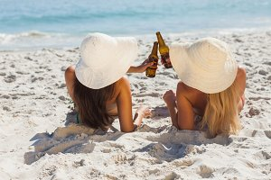Attractive blonde and brunette in bikinis clinking glass bottles