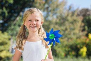 Young blonde girl holding pinwheel smiling at camera