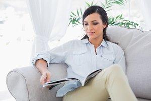 Peaceful gorgeous brunette reading magazine