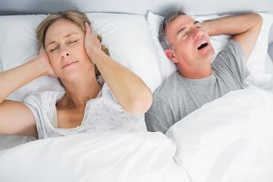 Wife blocking her ears from noise of husband snoring