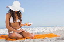 Attractive dark haired woman applying sun cream while sitting on her towel