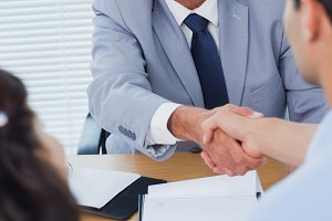 Serious real estate agent shaking hands with his new buyer