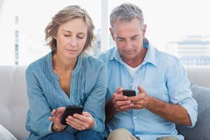 Smiling couple using their smartphones