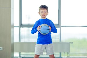 Little boy playing basketball blue ball and form