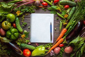 Notepad surrounded fresh vegetables