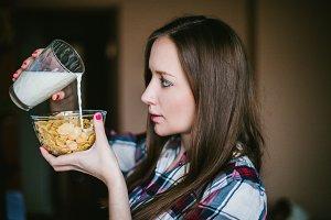 The girl pours milk flakes