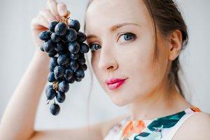 A girl holds a black grape