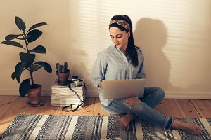 Pretty hipster young woman using a laptop