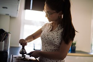Young woman making a cup coffee in kitchen