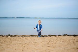 Little boy playing on the river bank
