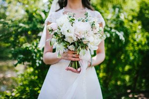 The bride holds a white wedding bouquet