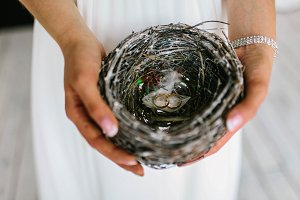 The bride holds a nest with wedding rings