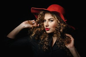 Girl with curly hair in red hat