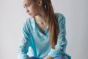 Confident stylish urban young woman looking away while sitting on chair, on gray background