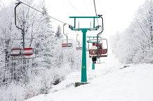 Skiers on ski-lift in snow mountains