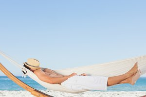 Man wearing straw hat relaxing in a hammock