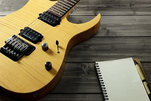Guitar on Wooden Top & Paper Notepad