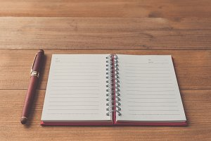 a pen and blank notebook