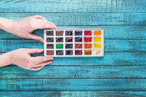 hands holding paints