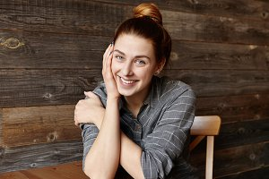 People and lifestyle concept. Portrait of good-looking girl with cute smile posing indoors against wooden wall background. Attractive young Caucasian woman with hair bun relaxing at cafe alone