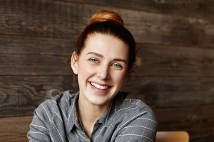 Headshot of cute girl with hair bun spending lunch break at c restaurant with wooden walls, sitting alone and waiting for her friends. Happy cheerful Caucasian woman with joyful smile posing indoors