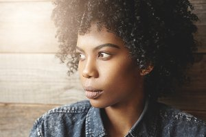 Close up portrait of fashionable dark-skinned girl with Afro hairstyle and healthy perfect skin wearing stylish denim shirt relaxing indoors, posing isolated at wooden wall background. Flare sun