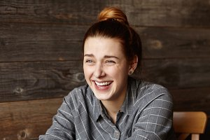 Stylish young redhead woman wearing grey checkered shirt laughing out loud while having fun indoors. Headshot of attractive girl with happy smile, sitting alone against wooden wall background