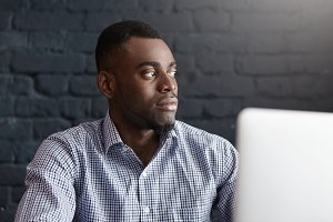 Isolated shot of serious young dark-skinned male freelancer wearing blue checkered shirt using laptop for remote work, having lunch at modern cafe, looking away with confident facial expression