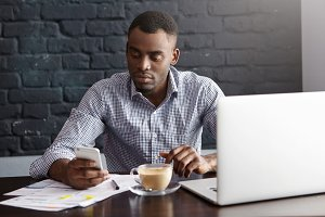 Attractive young dark-skinned entrepreneur having serious look texting message on mobile phone, using free wireless internet connection while doing paperwork during coffee break at restaurant