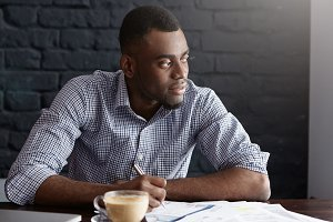Portrait of attractive young African-American CEO in shirt going through some paperwork, sitting at cafe table with documents and mug, making notes with pen and looking away with pensive expression