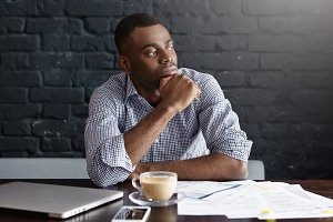 Serious African-American businessman having coffee at cafe, sitting at table with laptop, mobile phone and documents, working on financial report, holding hand on his chin with thoughtful look