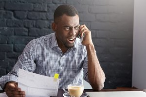 Angry African businessman in formal shirt having furious look, holding piece of paper, yelling at mobile during phone conversation with his employees while drinking cappuccino at coffee shop