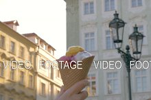 View of unfocused cityscape on the background and then seen ice cream balls in the waffle cup, Prague, Czech Republic