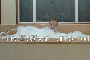 Playful child having bath with foam