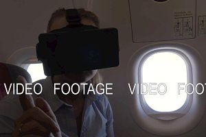 View of woman using VR-helmet for smartphone in airplane