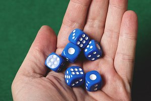 Blue dice on a hand. Isolated.