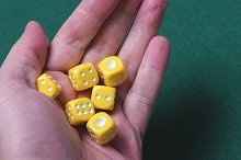 Yellow dice on a hand. Isolated.