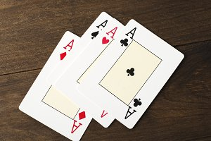 Four poker cards on wooden table. Four aces. Horizontal shoot.