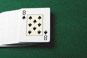 Deck of poker cards on green background. Horizontal shoot.