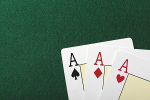 Three aces on the green table of a casino. Poker.