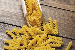 Wooden spoon with macaroni on wooden table.