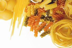 Background of a wooden spoon with macaroni next to several types of pasta. Copy space.